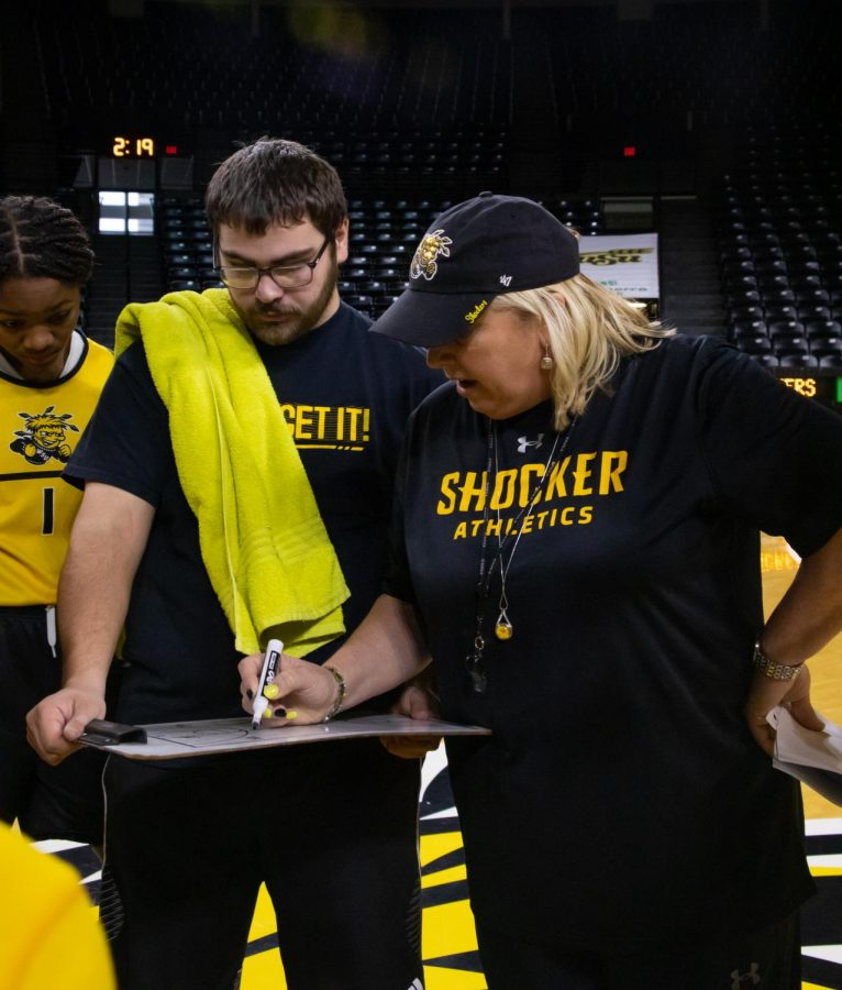 Neil Terry, a manager for the Wichita State women's basketball team, holds a white board for Head Coach Keitha Adams as she draws up a play during practice. Terry's late mother was high school best friends with Adams.