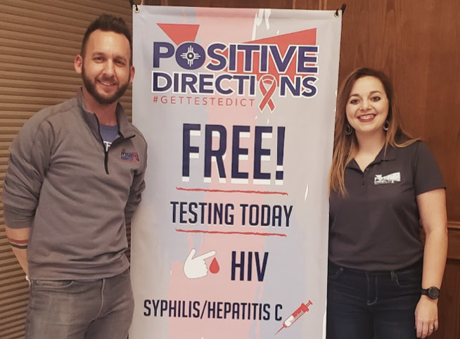 Positive Directions Executive Director Brett Hogan (left) and Outreach Coordinator Stephanie Kreutzer stand by a sign advertising free STI testing.