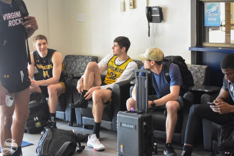 Wichita States Jacob Herrs and Tate Busse sit with Marcus Wright after receiving the news of the AAC Tournament cancellation on Thursday, March 12.