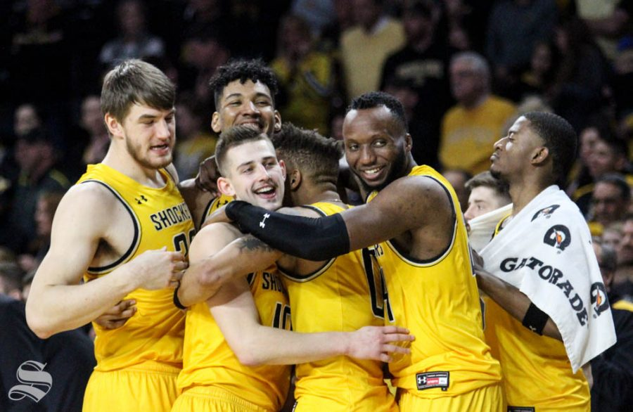 Wichita State players embrace senior Jaime Echenique as the clock expires during the game against Tulsa on March 8 inside Charles Koch Arena.