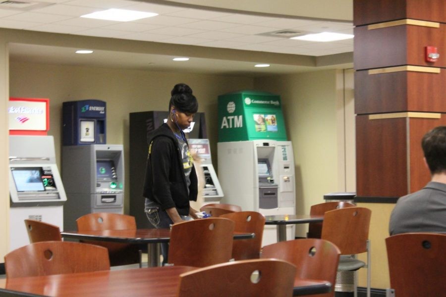 A member of the Rhatigan Student Center custodial staff wipes down tables by Starbucks.