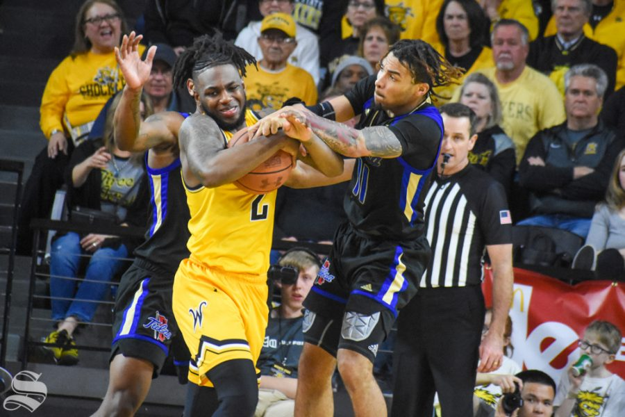 Wichita States Jamarius Burton and Tulsas Darien Jackson wrestle for the ball during the game on Sunday, March 8 inside Charles Koch Arena.