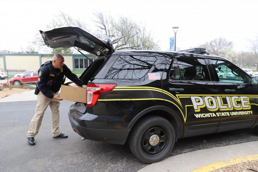 Wichita State Police Sergeant Christopher Tenet unloads a box of personal protective equipment from his police vehicle. Tenet made a delivery to the University of Kansas Medical Center on March 27, 2020.