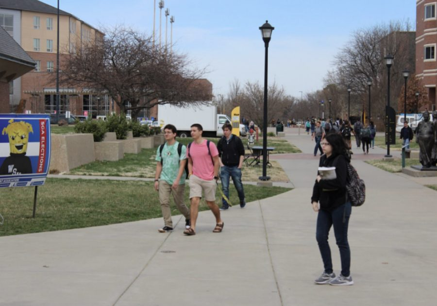 Students walk across campus before it closed for the semester because of COVID-19. Campus, county, and state officials warn that the population of 20 to 44-year-olds are at higher risk for catching and spreading the virus than they may think.