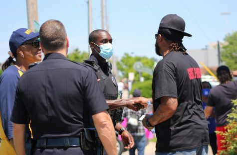 A protester shakes hands with a police officer during a protest against police brutality on Saturday outside of the Wichita police station on 21st Street. The peaceful protest was one in a string of demonstrations across the nation after George Floyd died at the hands of the police.