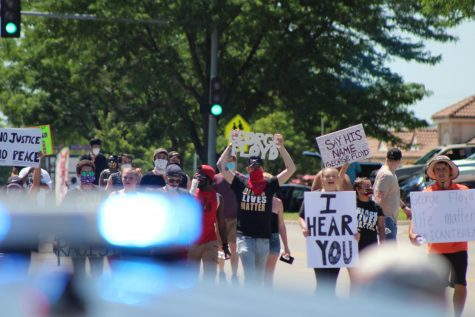 Protesters march on Saturday toward the Wichita Police Department building on 21st Street near Wichita State