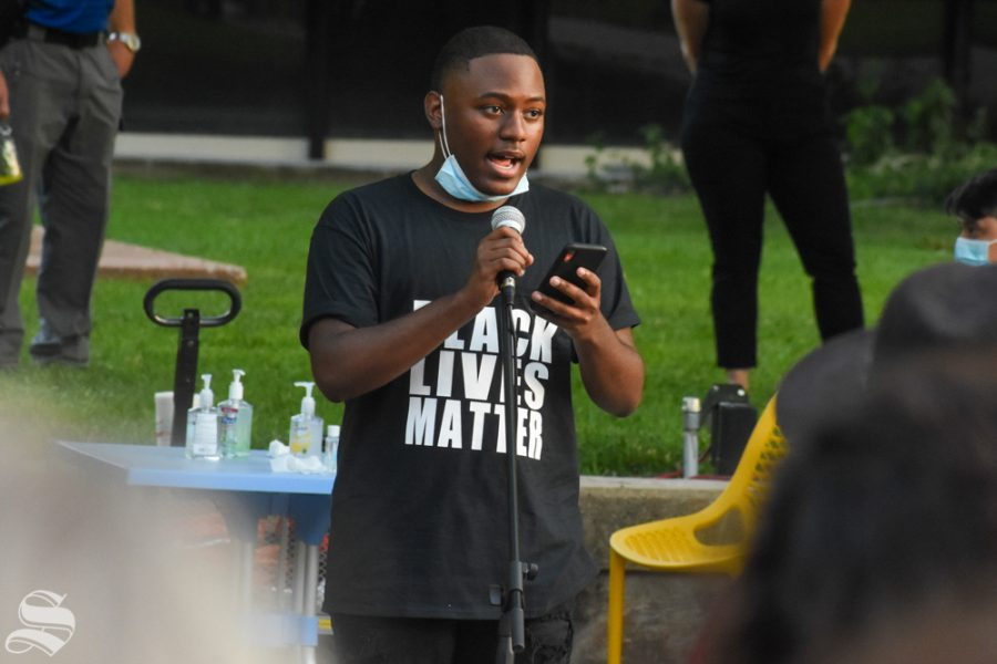 Neiman Thompson, Greek relations director for the Multicultural Greek Council, speaks during a candlelight vigil Friday night in the MGC Quad. Thompson was one of four speakers at the event.
