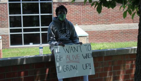 A demonstrator holds a sign during a protest on Saturday outside of the Wichita police station near WSU.