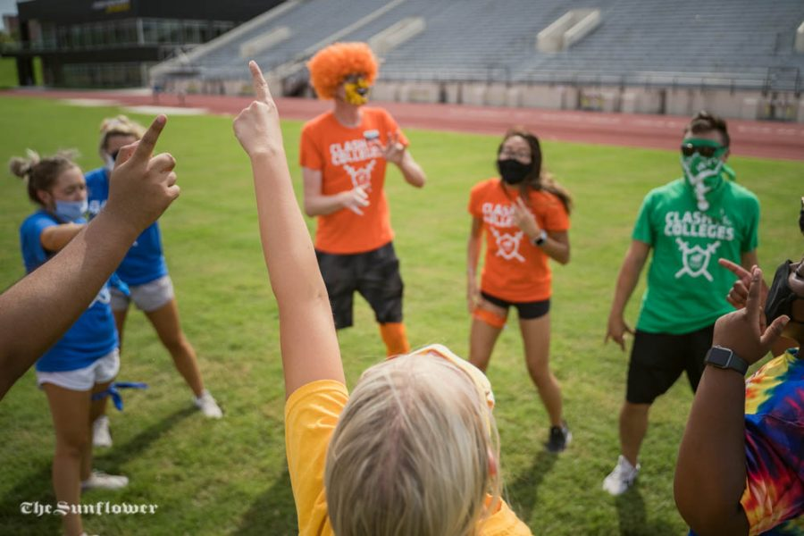 Event staff members warm up before the start of Clash of the Colleges. The event was held on Friday, Aug. 21 at Cessna Stadium.
