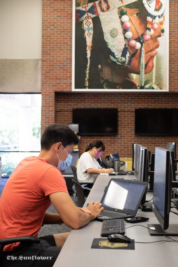 Senior, Elio Lago is using his laptop at the Ablah Library while practicing social distancing. Certain computers in the library have signage that prohibits students from working side by side with each other.
