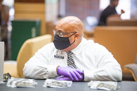 Aaron Austin, Dean of Students, passes out masks on the first day of fall classes inside the RSC on August 17.