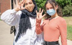 Wichita State students Emaan Syed (left) and Lena Alhallaq (right) pose with their masks while holding up the shocker hand sign on Thursday, Aug. 27 outside of Clinton Hall.