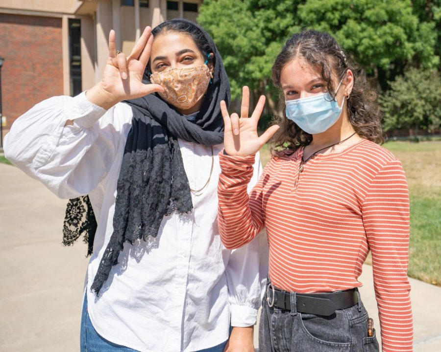 Wichita+State+students+Emaan+Syed+%28left%29+and+Lena+Alhallaq+%28right%29+pose+with+their+masks+while+holding+up+the+shocker+hand+sign+on+Thursday%2C+Aug.+27+outside+of+Clinton+Hall.