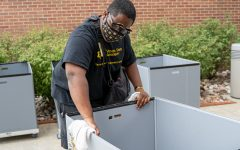 Omar Brantley, a volunteer at Shocker Hall, wipes down carts used to transport residents' belongings on Monday afternoon. More than 1,000 students are moving into residence halls this month.