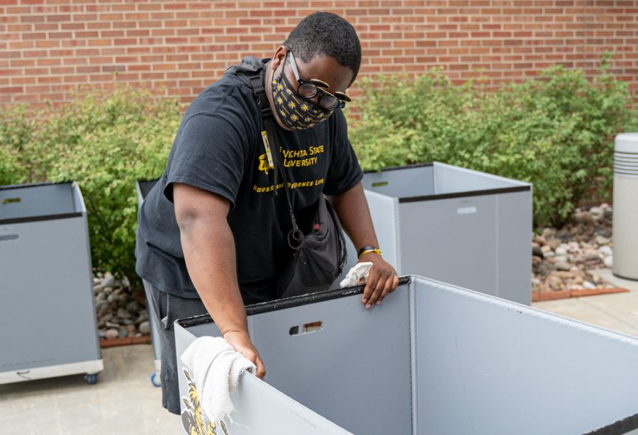 Omar Brantley, a volunteer at Shocker Hall, wipes down carts used to transport residents