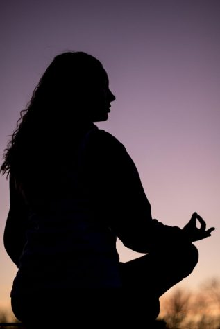 Kelsey Shingler poses for a photo sitting in a meditation position.