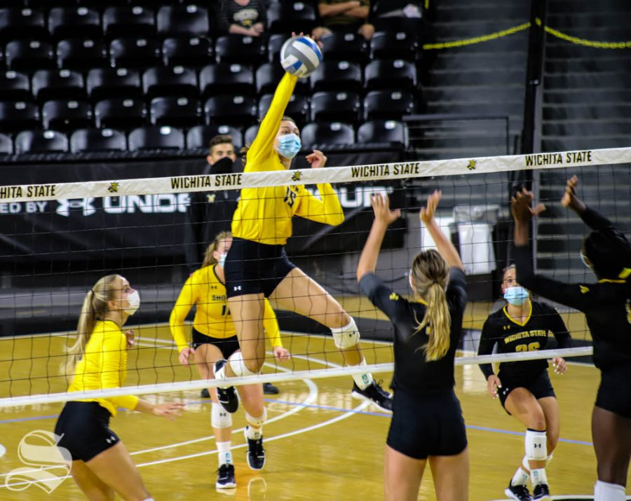 Freshman Morgan Stout spikes the ball over the net during the Black and Yellow Scrimmage at Charles Koch Arena.