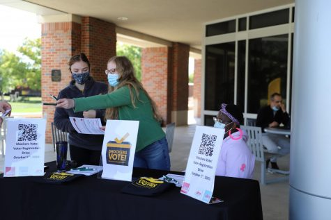 Students Ella Ihrig, Ella Perkins and Kamilah Gumbs help a WSU student register to vote during the Shockers Vote! Coalition tabling event outside the Rhatigan Student Center on Monday, Oct. 5.