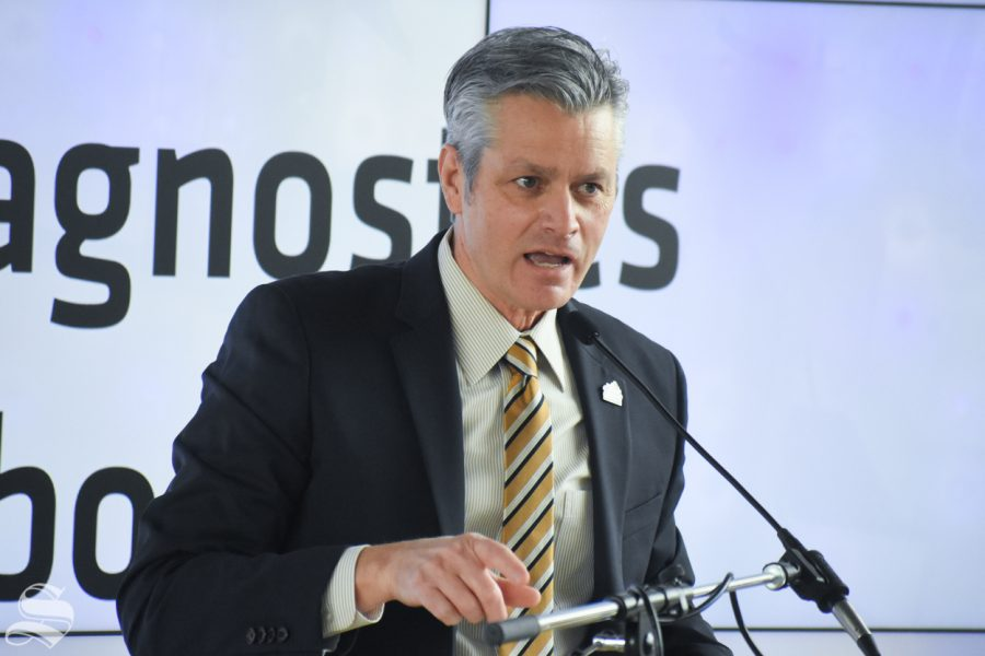 Interim President Rick Muma introduces the Governor of Kansas, Laura Kelly, during the opening of the new Molecular Diagnostics Lab on Monday inside the John Bardo center on Innovation Campus.