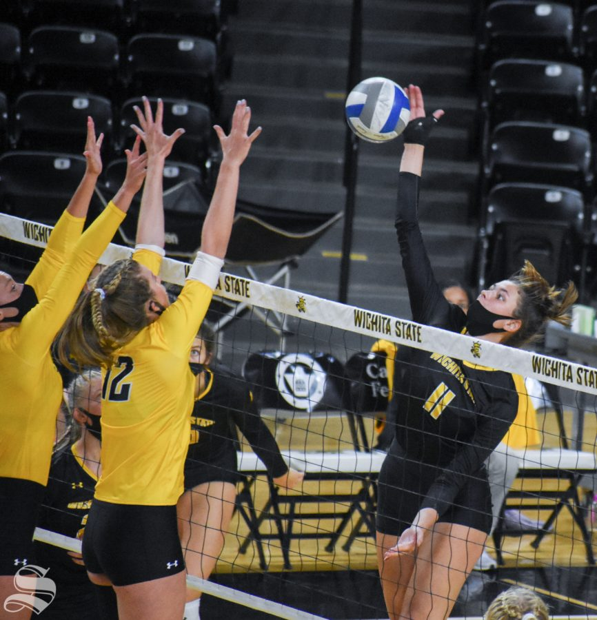 Wichita States Natalie Foster goes up for a spike while redshirt junior Megan Taflinger and freshman Lauren McMahon double block during the Black and Yellow Scrimmage on Friday, Oct. 16 inside Charles Koch Arena.