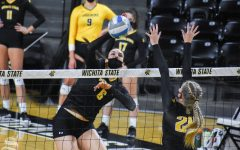 Senior Emma Wright spikes the ball while yellow team defender, Hailey Plugge blocks at the net during the scrimmage on Friday.