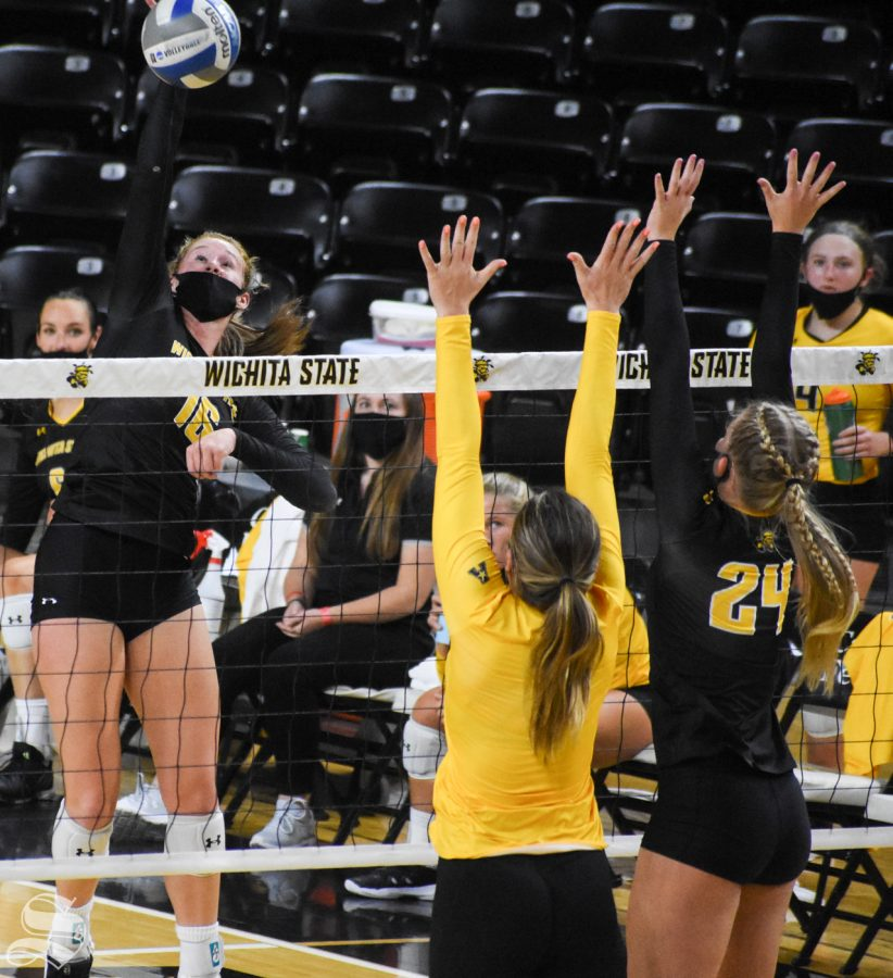 Freshman Marriah Buss spikes the ball while yellow team defenders block at the net during the Black and Yellow Scrimmage on Friday inside Charles Koch Arena.