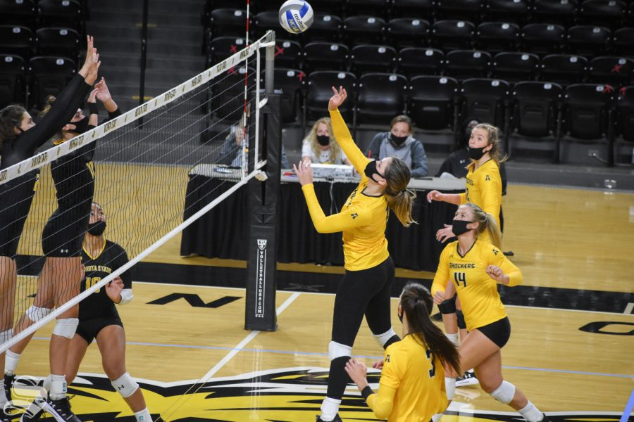 Sophomore Nicole Anderson tips the ball over to the black side during the Black and Yellow Scrimmage on Friday.