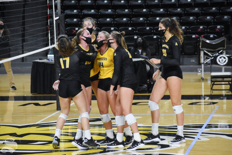 The black team celebrates after scoring against the yellow team in the fifth set during the Black and Yellow Scrimmage on Friday, Oct. 16.