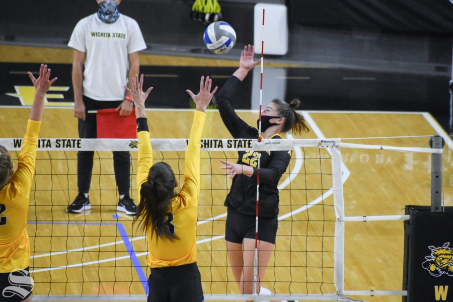 Wichita State freshman Morgan Weber goes up for a spike while yellow team defends prepare to block during the Black and Yellow Scrimmage on Friday inside Charles Koch Arena.