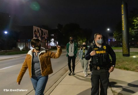Sergeant Johnson from the University Police Department and senior Olivia Babin point out broken lights during the Safety Walk around Wichita State campus on Oct. 20.