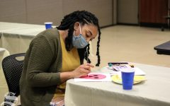 A student paints a skull for the Day of the Dead themed First Friday.