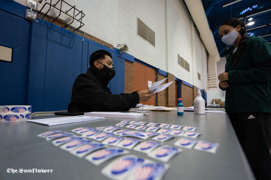 Volunteer Francisco Median helps out a voter at Boston Recreation Center on Tuesday.