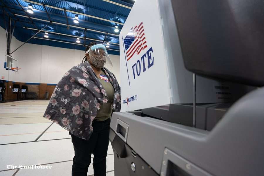 Volunteer Makayla Holmes helps out a voter at Boston Recreation Center on Tuesday.