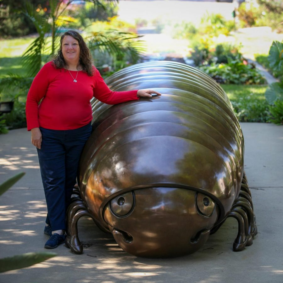Carolyn Copple stands next to Millie the Millipede on the Wichita State University campus.