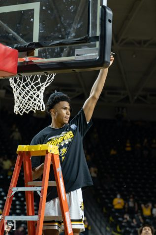 Wichita State freshman Ricky Council IV cuts the net celebrating Wichita State first AAC regular season title on March 6 at Charles Koch Arena.