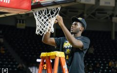 Wichita State redshirt freshman Josaphat Bilau cuts the net celebrating Wichita State first AAC regular season tittle on March 6 at Charles Koch Arena.