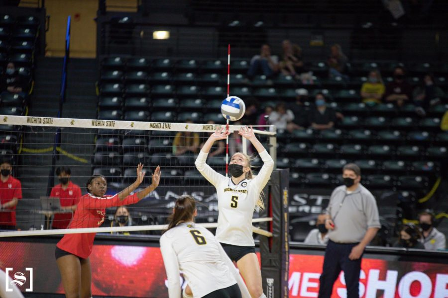 Sophomore Kayce Litzau sets the ball in WSU's game against Houston on March 26 inside Charles Koch Arena.