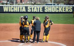 Wichita State players talks with head coach Kristi Bredbenner during the game against ECU at Wilkins Stadium on Mar. 28, 2021.