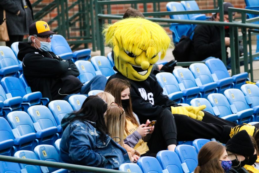 Wichita State baseball fans sit in the stand with Wu Shock during a game against Kansas University at Eck Stadium on March 23.