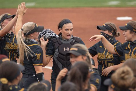 Wichita State senior Madison Perrigan gathers with her teammates during the game against Oklahoma State at Wilkins Stadium on April 27, 2021.