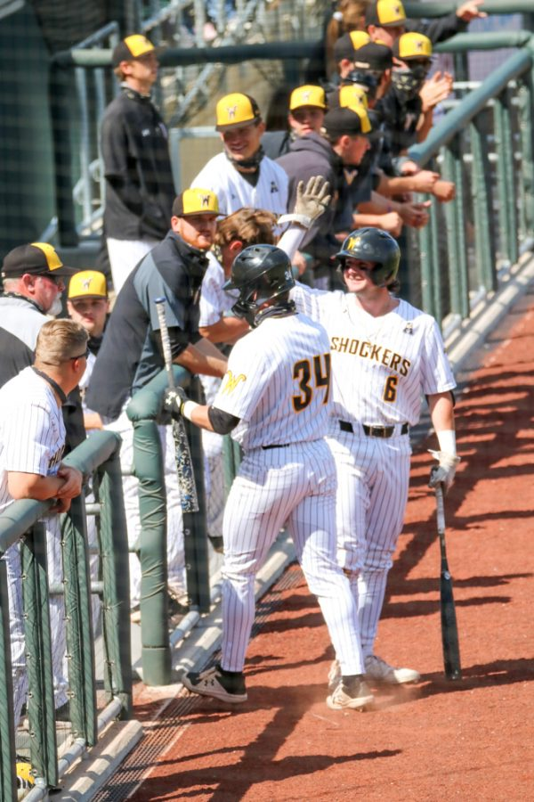 Wichita State players, Corrigan Bartlett and Jack Sigrist high five in celebration during a game against Houston at Riverfront Stadium on April 10.