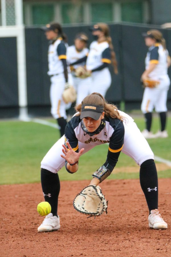 Wichita State junior, Neleigh Herring bends down to catch the ball while warming up for a game against USF at Wilkins Stadium on April 23.