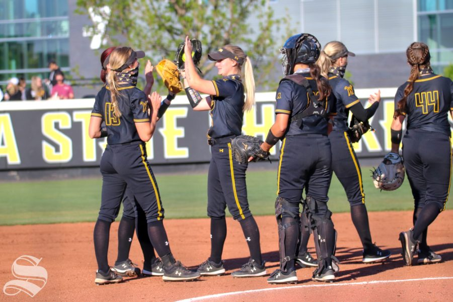 Wichita State softball players have a little pep talk equipped with high fives all around during a game against University of Oklahoma at Wilkins Stadium on April 4