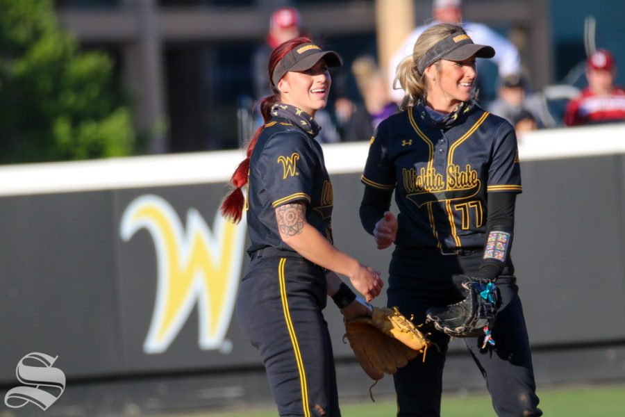 Wichita State softball players, Sydney McKinney and Kaylee Huecker share a laugh during a game against University of Oklahoma at Wilkins Stadium on April 4
