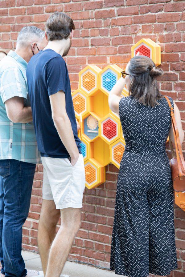 visitors look at Honeybee Hideaway created by Laura Shank at Gallery Alley on July 2, 2021.