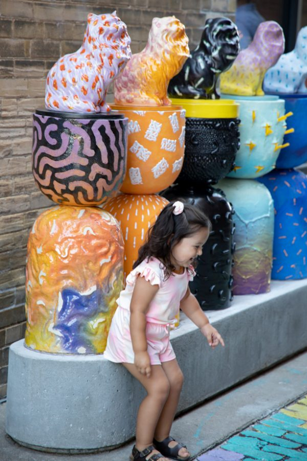 A little girl pretends to be a cat in front of Alley Cats created by Armando Minjarez at Gallery Alley on July 2, 2021.