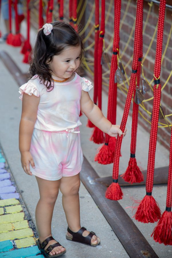 A little girl plays with the cord of the Rythm Maker! created by Mike Miller at Gallery Alley on July 2, 2021.