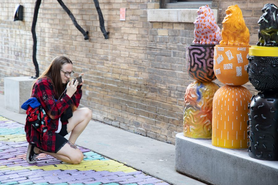 A woman takes a picture of Alley Cats created by Armando Minjarez at Gallery Alley on July 2, 2021.