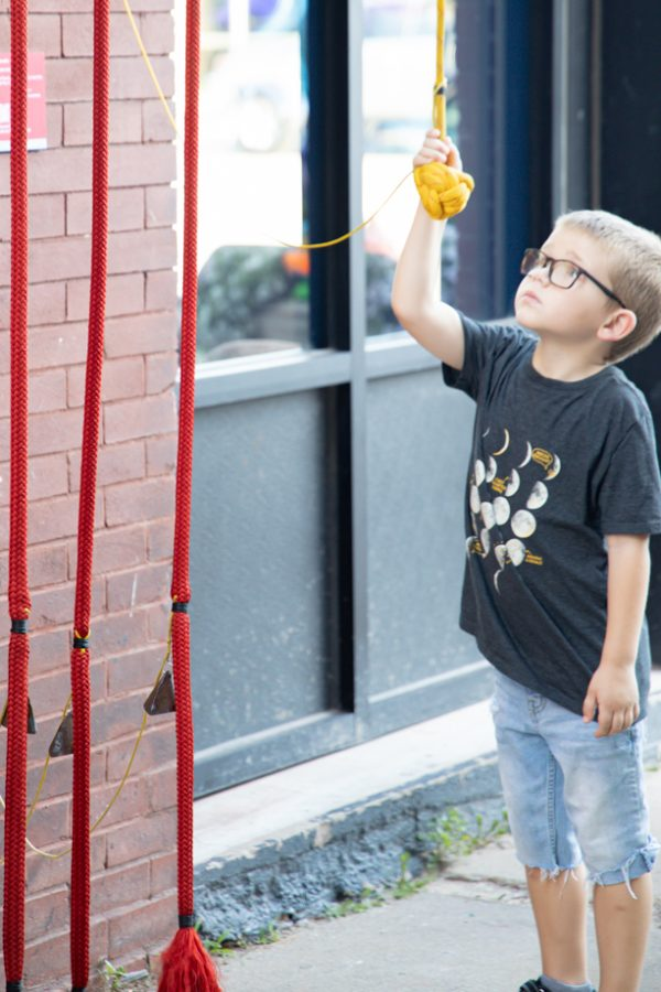 A little boy pulls the cord of the Rythm Maker! created by Mike Miller at Gallery Alley on July 2, 2021.