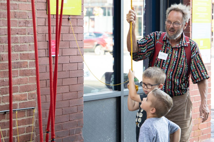 Mike Miller creator of the Rythm Maker! shows two boys how the art work operates at Gallery Alley on July 2, 2021.